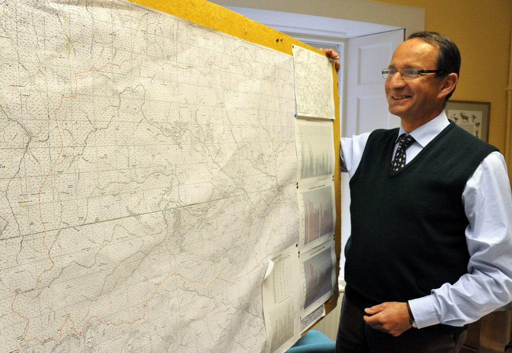 Richard Cooke, chairman of the Association of Deer Management Groups, stands before a deer distribution map at the association office in Brechin, Scotland.
