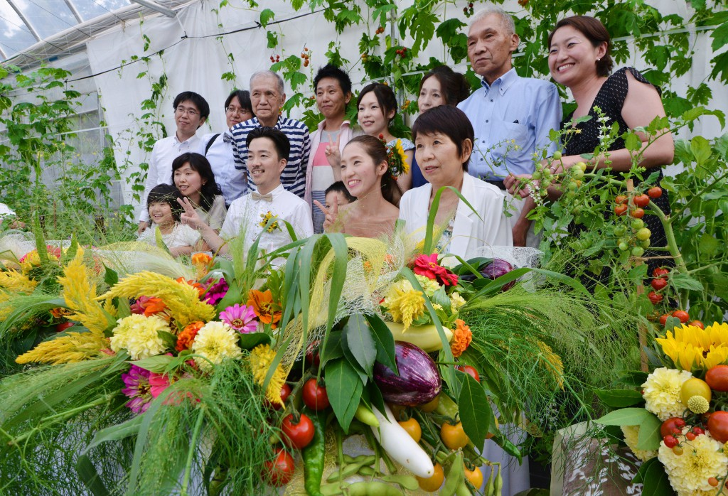 Happy pair (center) taking pictures with parents and relatives at head table decorated with flowers and vegetables. The arrangement uses more than 10 kinds of colorful vegetables including egg plants, tomatoes and green soybeans in pods.