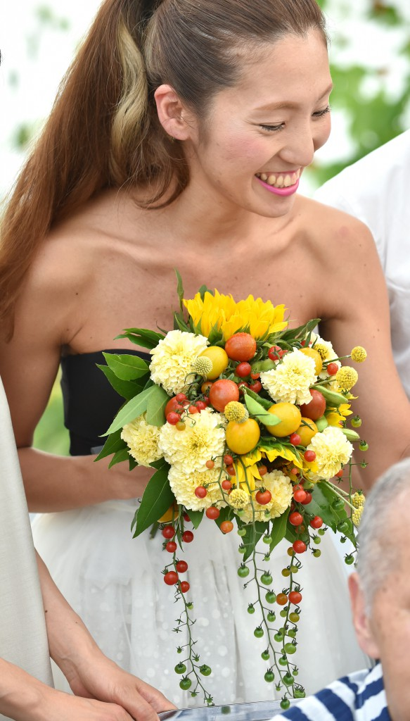 Hiromi Tokumoto, bride, with bouquet of sunflowers and grape tomatoes in different colors and sizes in hand
