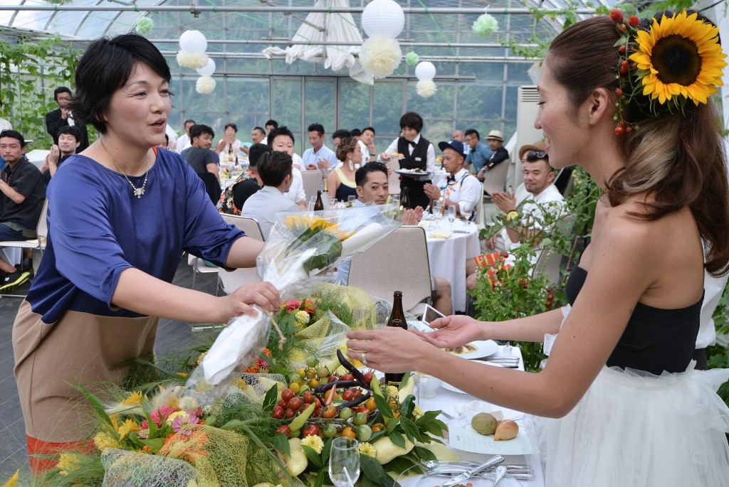 Michiyo Koyama (left) handing over flower bouquet for bouquet toss to bride (right). Koyama decorated venue with flowers and vegetables she sowed and grew.