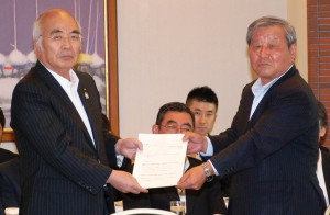 A photo taken on Friday, Aug. 8, provided by the Central Union of Agricultural Co-operatives (JA-Zenchu), shows JA-Zenchu President Akira Banzai (left) handing a letter to Kazuo Kimura, head of an advisory council, requesting the council to discuss reform of the JA group. (Courtesy of JA-Zenchu)
