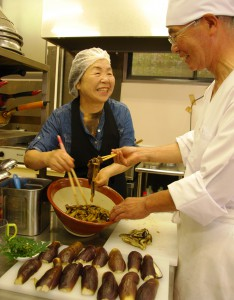 Imai (right) and Nonaka (left) tossing steamed eggplant with Sansho soy dressing. (Sasayama-shi, Hyogo Prefecture)