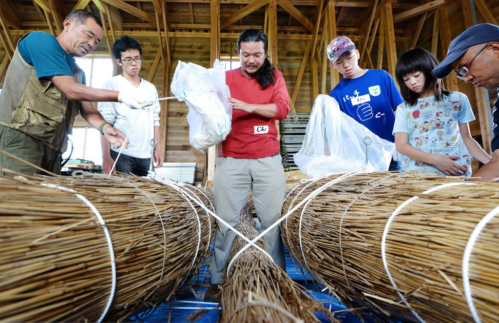 Professional adventurer, Jin Ishikawa, instructing boat building processes. Five parts are joined together by ropes to make boat.
