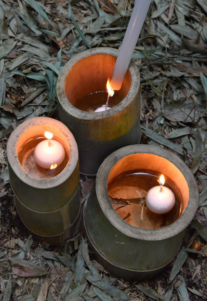 Lighting floating candles in bamboo cups.
