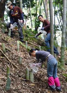 Volunteers preparing bamboo lanterns on steep slope.