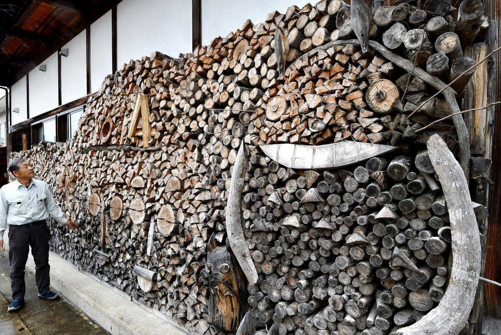 Tsukida creates woodpile mosaic under shallow eaves, using natural shapes of firewood. (in Minamiaizu-cho, Fukushima Prefecture)