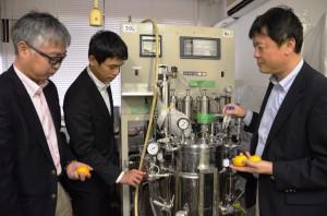 Professor Hiroshi Tamaru (right) and Associate Professor Junji Yoshii (left) show a device which can create 30 liters of biobutanol at Tsu, Mie Prefecture.