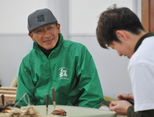Shingo Kojima, General Manager of Yatsushiro Central Rush Grass Producers Group of JA, observing artisan's work while having pleasant chat