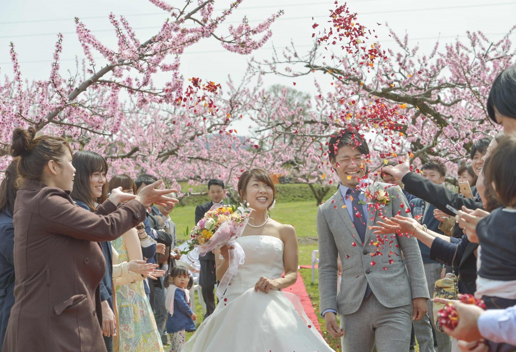Guests celebrating Jumpei and Akina with flower shower while they walk down open aisle (in Fuefuki-shi, Yamanashi Prefecture)