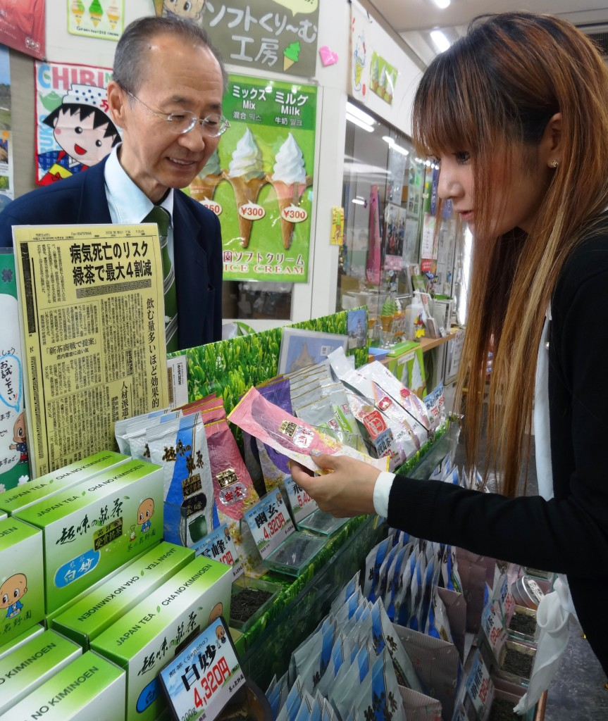 A young woman looks at a package of green tea leaves at a tea store in Tokyo's Taito Ward.