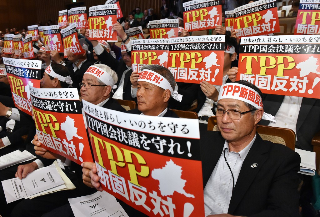 Representatives of the agricultural sector hold up posters calling on the government to protect farm products in the TPP talks at a rally held on Tuesday, May 19, in Tokyo's Minato Ward.