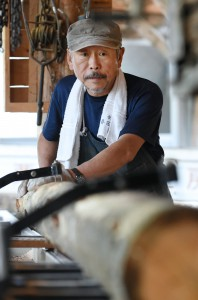 Yamada hand-cutting log into boards. He does everything from barking to lumbering.