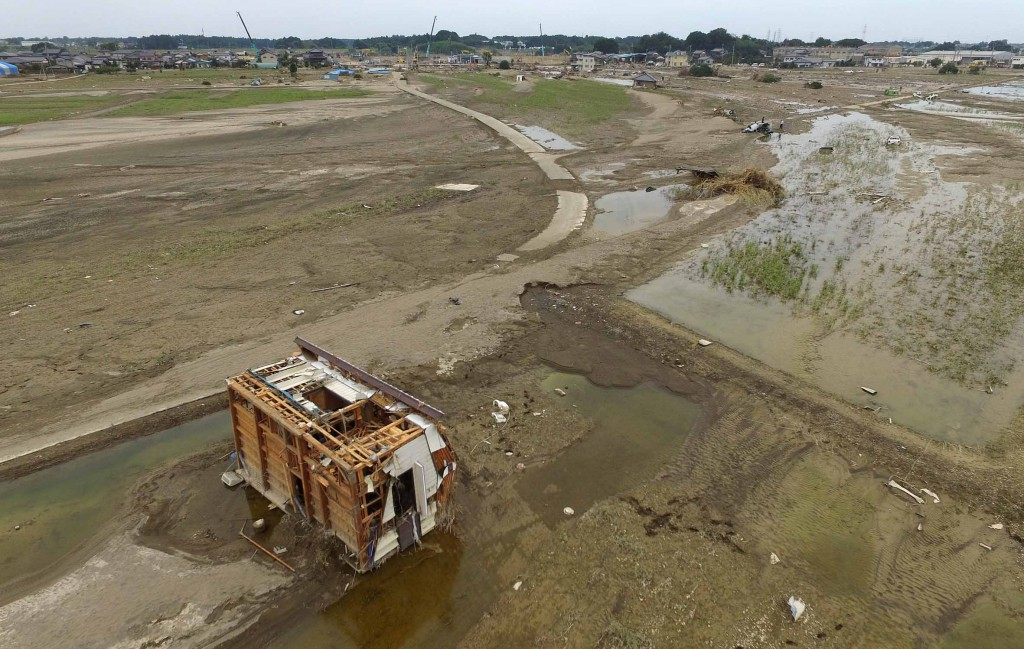 A house lies on its side on a farmland on Wednesday, Sept. 16, in Joso, Ibaraki Prefecture, after being swept away by the flood caused by the collapse of the Kinugawa River banks a week before. Damaged houses and vehicles are left on farm fields covered with mud, while numerous crane trucks are lined up along the riverbank to reconstruct the levee.