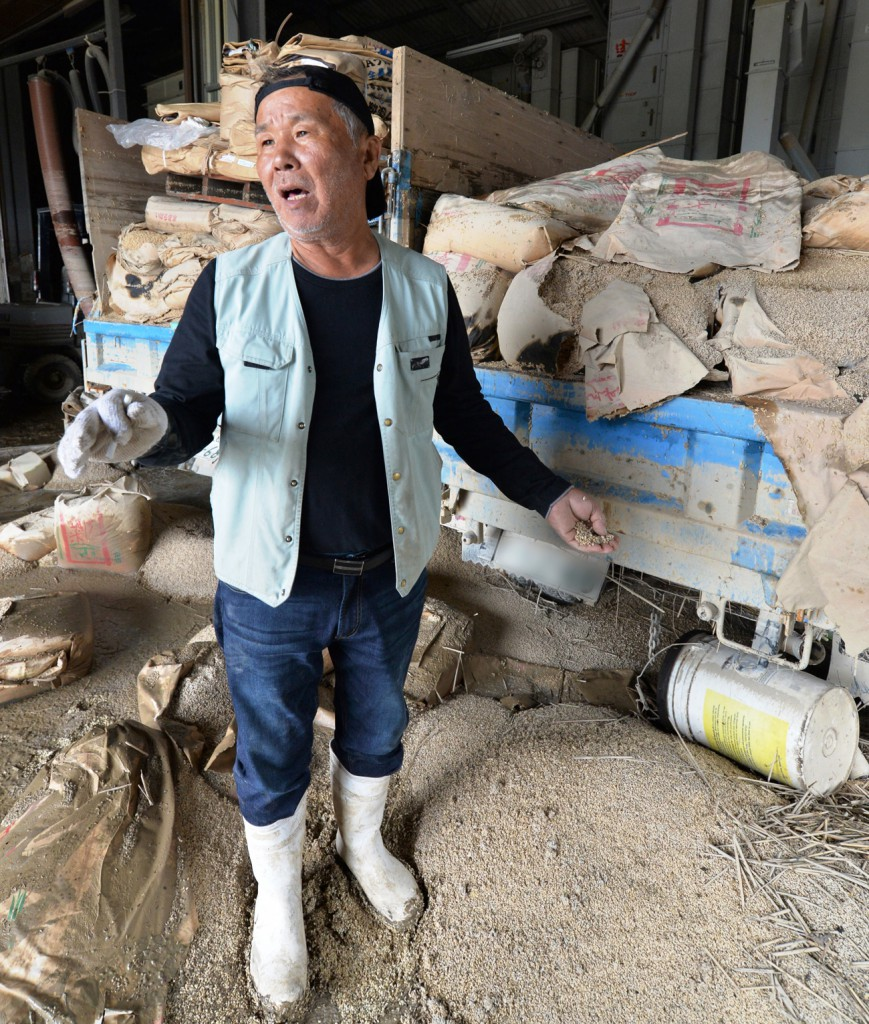 Isamu Wada shows bags of unmilled rice stored in his farm in Joso, Ibaraki Prefecture, on Wednesday, Sept. 16. The bags were soaked in muddy water as the flood hit the district. The Japan Agricultural News blurred the plate number of the car in this photo