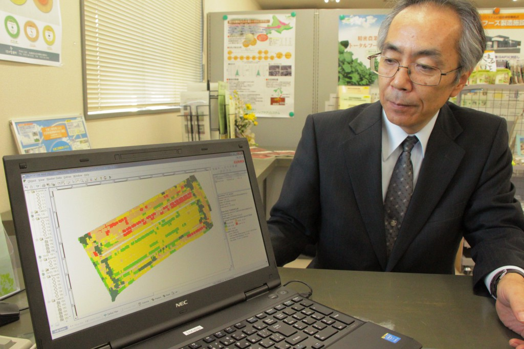 An official of Isopp Agri System based in Kitami, Hokkaido, shows a wheat crop yield map of a 2.6-hectare field on a computer