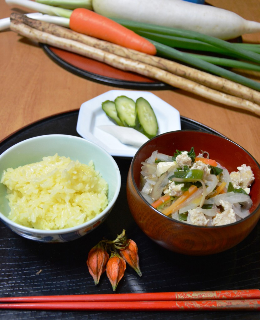 """Ohan"" yellow steamed rice colored with dried gardenia fruits and ""ohan kayaku"" topping containing several kinds of root vegetables"