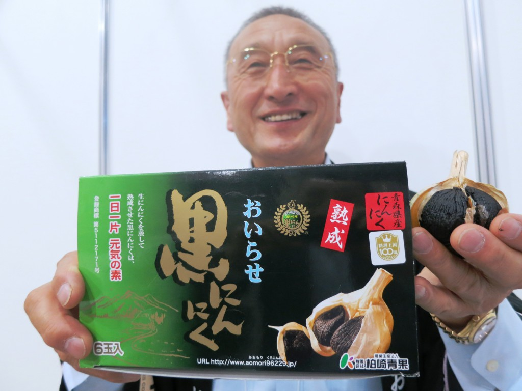 Shinichi Kashiwazaki, head of Kashiwazaki Fruit and Vegetables Corp., shows black aged garlic which the firm exports overseas.