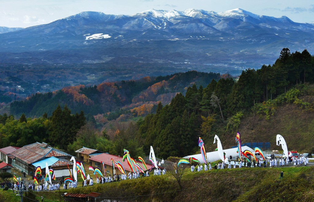 Villagers holding tall colorful banners walk in procession on the mountain pathway of Kohata.  Mt. Adatara behind them is slightly covered with snow. (in Nihonmatsu, Fukushima Prefecture)