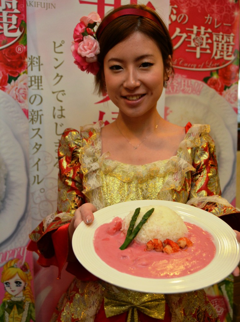 A woman displays pink curry and rice colored by beetroots grown in Tottori Prefecture. Café Oenokian in Tottori also offers a dress rental service to let visitors get dressed in Rococo costumes just like the characters promoting the café